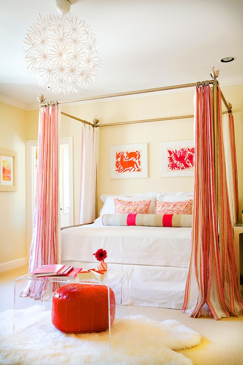 metal canopy bed with pink and beige striped curtains