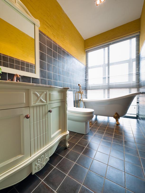 Stylish yellow and dark-tone bathroom with white cabinets
