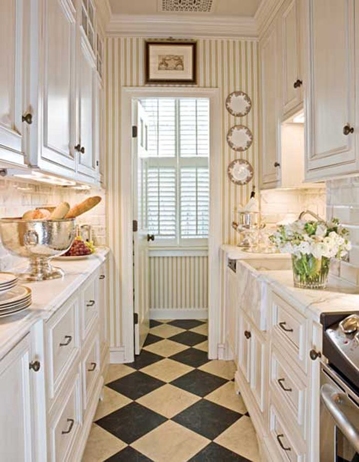 galley kitchen in white with marble counters. harlequin floors