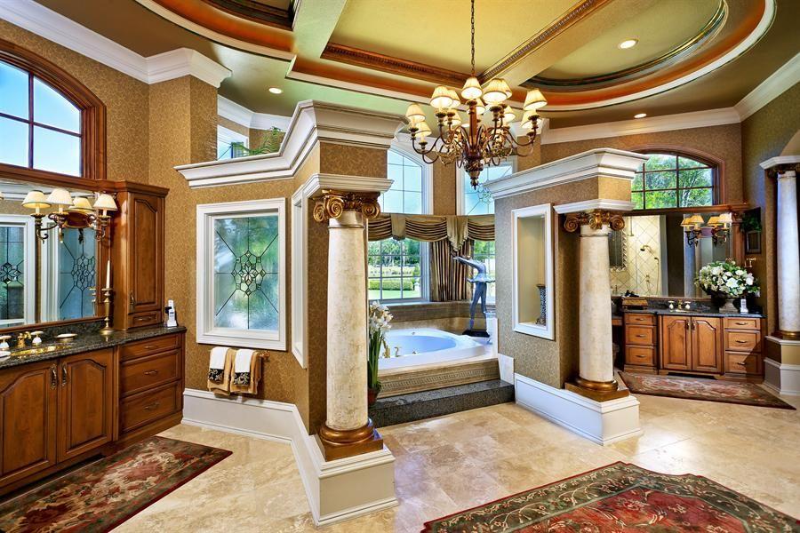 Large Mediterranean master bathroom with tray ceiling, drop-in tub and limestone tile floors