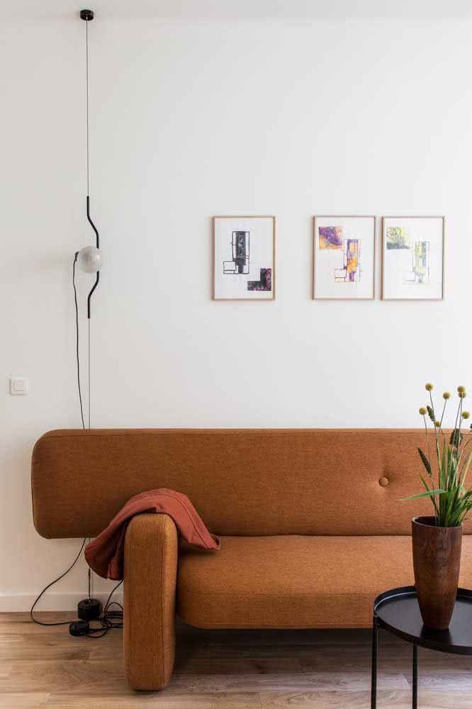Brown sofa of clean and modern design contrasting with the white wall of the room.