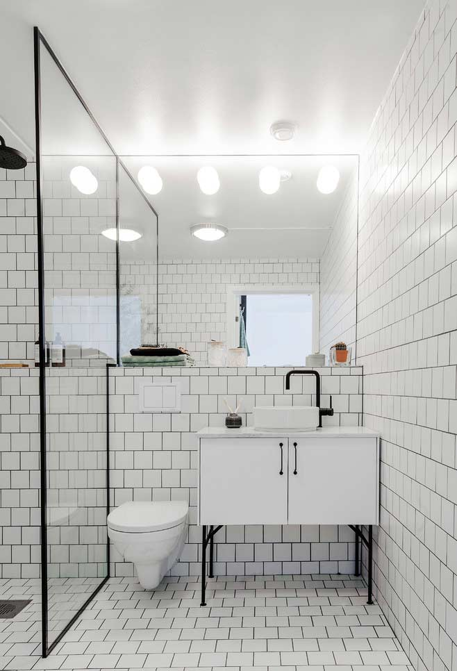 Subway tiles rectangular tiles in continuity on the walls and floor – minimal details in black on the joints
