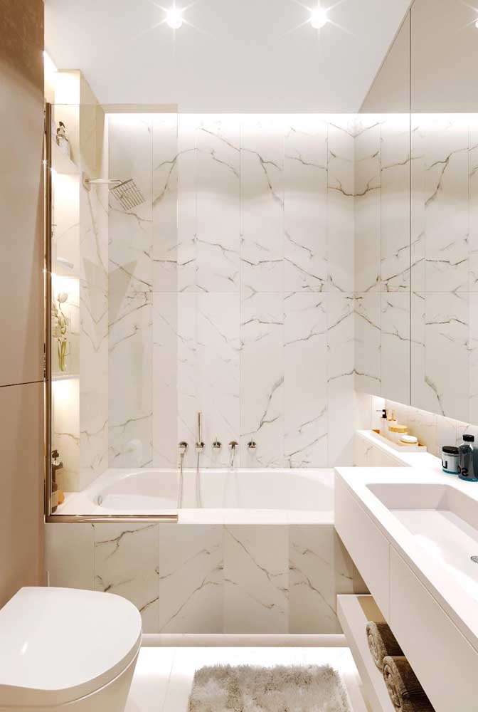 The small bathtub is highlighted with marble cladding and indirect lighting.