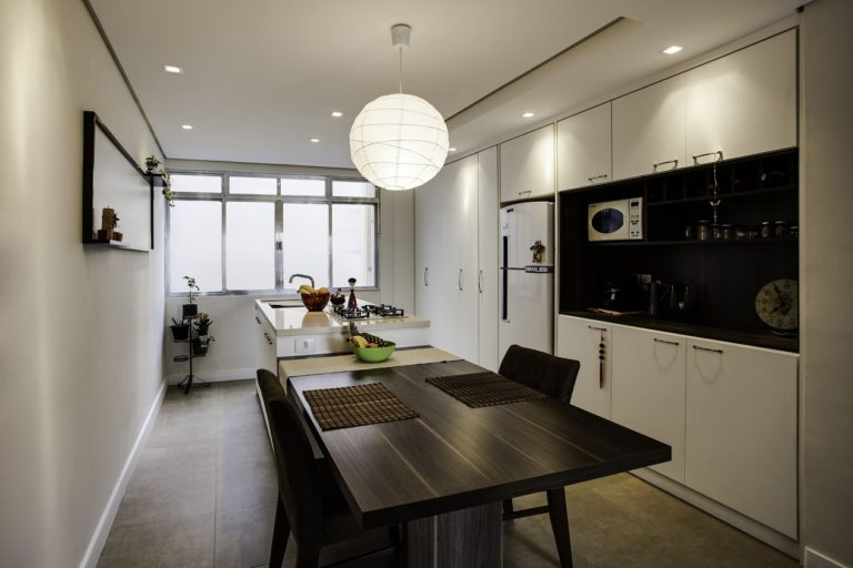 27. Central island with white counter, sink and dining table