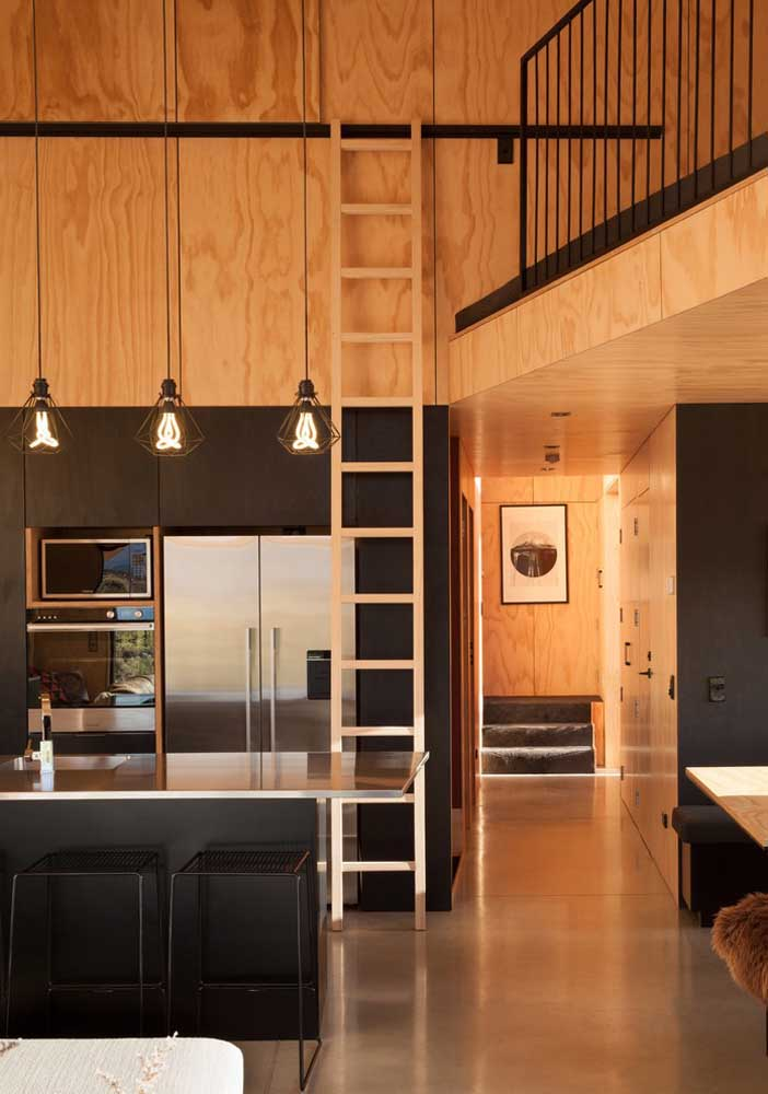 40. Different, this small American kitchen is integrated into the mezzanine by the stairs on the rail; the black furniture harmonizes with the wood used in the cladding of the house.