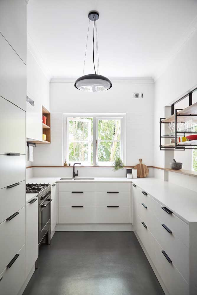 47. Small U-shaped kitchen with white cabinets and drawers.