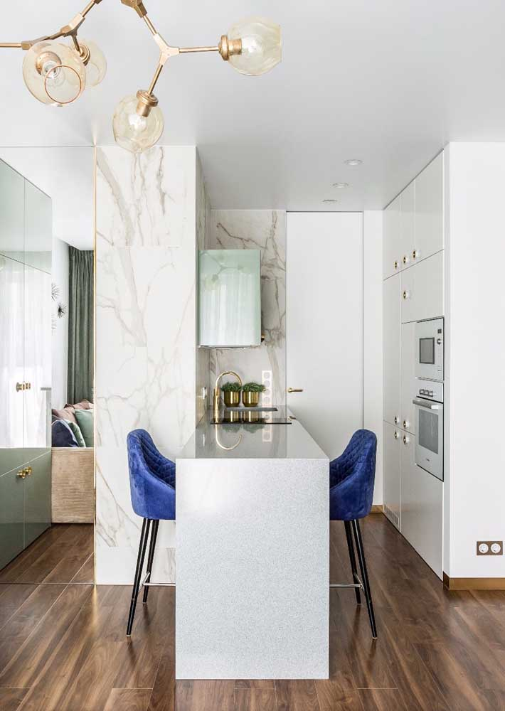 30. Although small, this American kitchen has managed to demonstrate that elegance and sophistication are not measured in square meters; notice the marble counter and the blue upholstered stools.