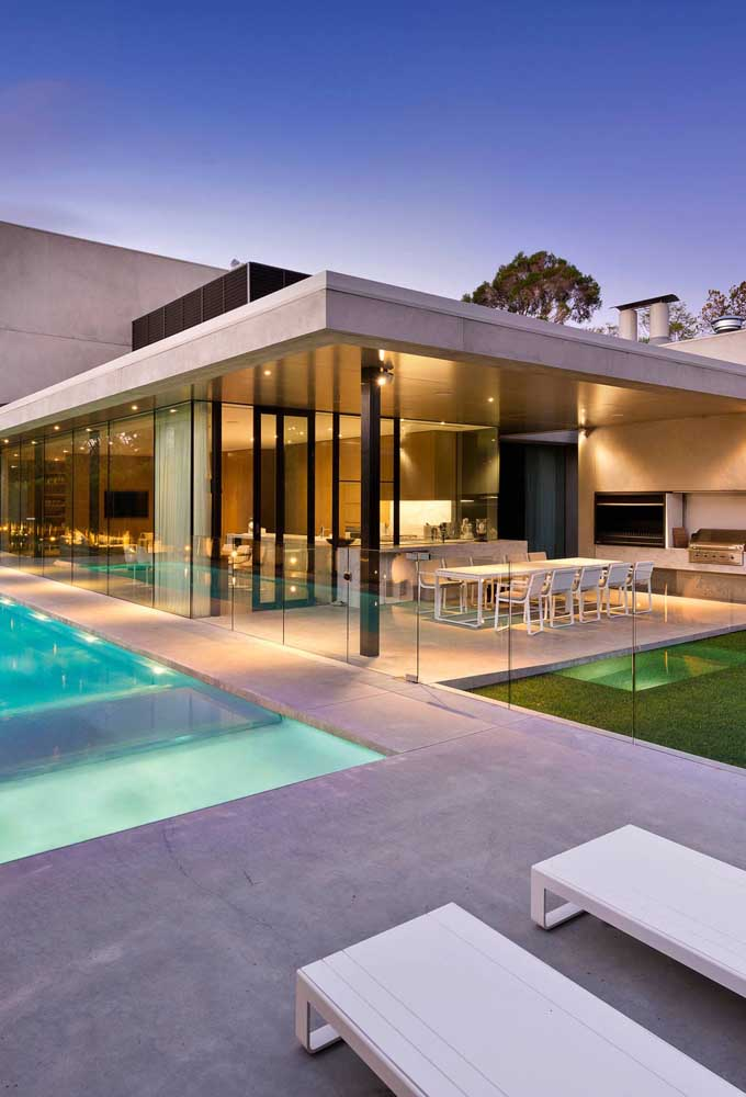 13. Leisure area with barbecue outside the house with a glass guardrail delimiting the space between the pool.