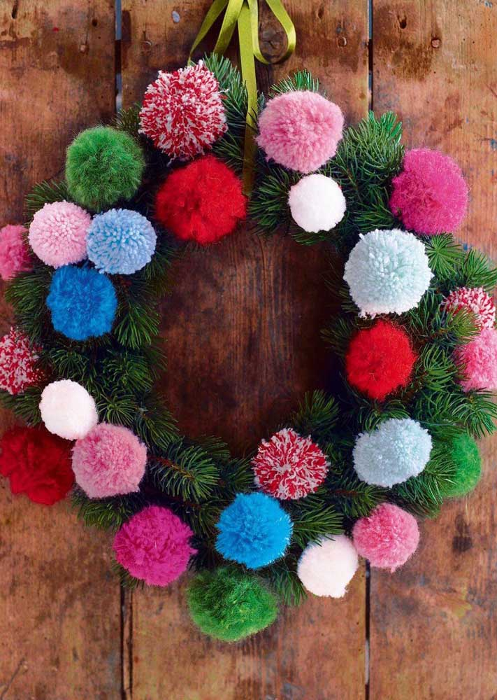 39. Pine branches and wool pompoms come together in this other Christmas wreath design.